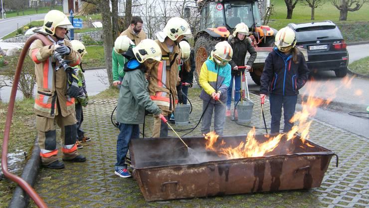 Schüler und Feuerwehr beim Feuerlöschen.