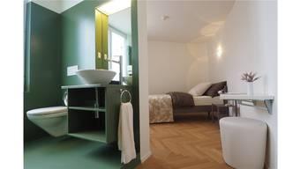 Blick in ein Einzelzimmer im 2. Stock, dessen Badzimmer neu grün gestrichen wurde. Dafür ist der Parkettboden hundertjährig.
