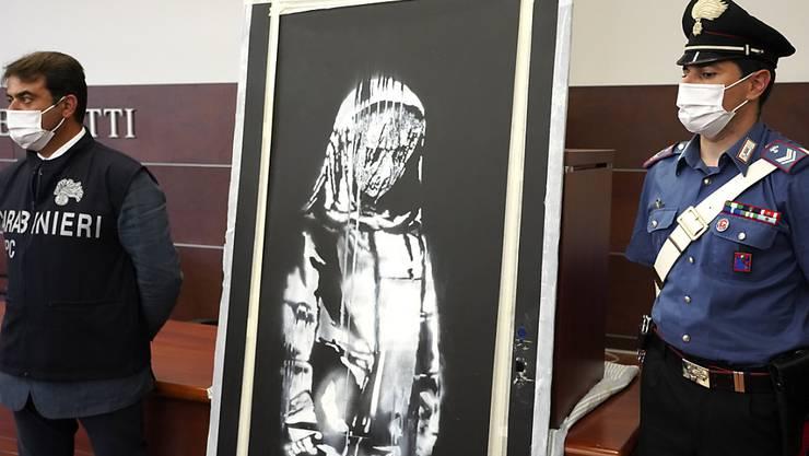 ARCHIV - Beamte der Carabinieri stehen neben der gestohlenen Tür aus der Pariser Konzerthalle Bataclan, auf der ein dem Streetart-Künstler Banksy zugeschriebenes Graffiti zu sehen ist. Es seien bereits Personen ermittelt worden, die mit dem Diebstahl und der «Reise» des Werkes zu tun gehabt hätten. Foto: Andrea Rosa/AP/dpa - ACHTUNG: Nur zur redaktionellen Verwendung im Zusammenhang mit der aktuellen Berichterstattung und nur mit vollständiger Nennung des vorstehenden Credits