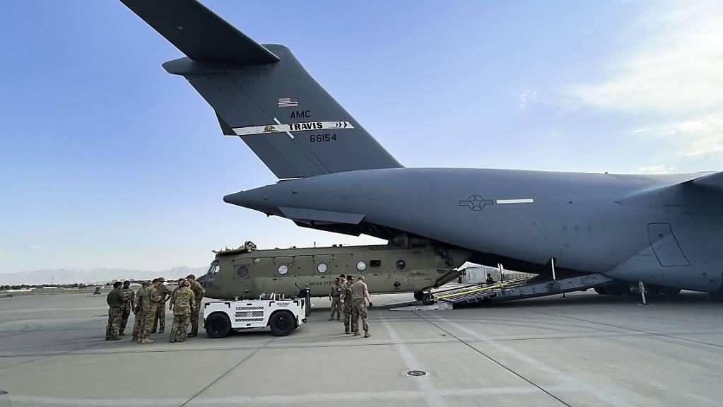 Ein Transporthubschrauber des US-Militärs wird auf dem Kabuler Flughafen in ein Militärtransportflugzeug verladen.
