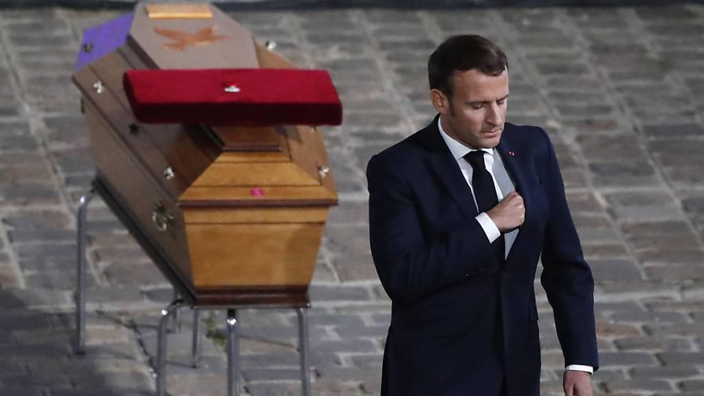Der französische Staatspräsident Emmanuel Macron wendet sich bei der Gedenkveranstaltung  für Samuel Paty vom Sarg des ermordeten Lehrers ab. Foto: Francois Mori/AP/dpa