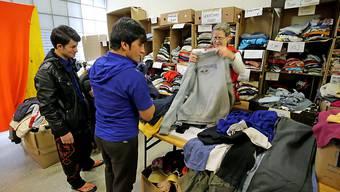 Flüchtlinge erhalten Kleider in einem Asylzentrum. Wer aber mit Vermögen in die Schweiz kommt, muss dieses abgeben, um damit die Kosten des Asylverfahrens zu decken. Etwas ähnliches will nun auch Dänemark einführen. (Symbolbild)