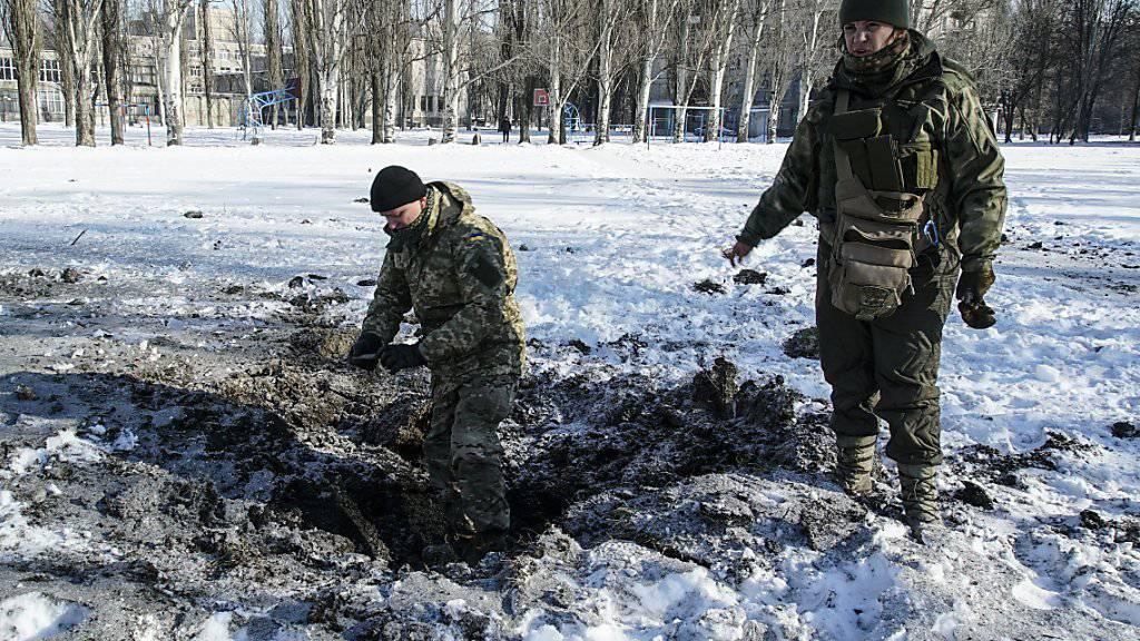 Ukrainische Soldaten begutachten den Krater einer Explosion in der Stadt Awdiiwka im Osten der Ukraine. (Archivbild)