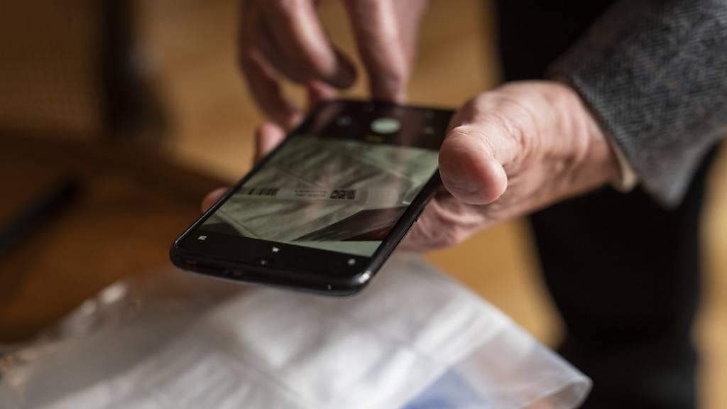 Eine Testperson registriert mit ihrem Smartphone den PCR Covid-19 Test. (Archivbild)