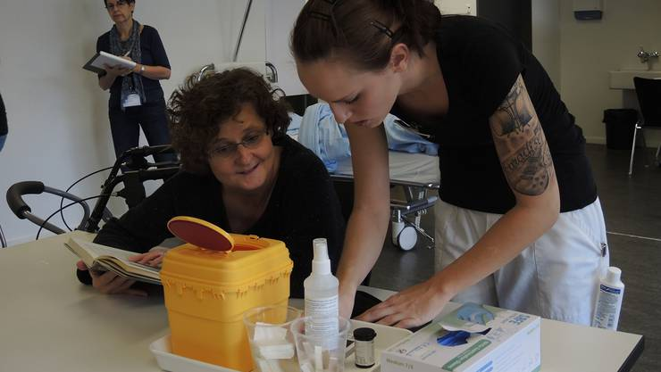 Die Fachangestellte Gesundheit Linda Häfeli bereitet den Blutzuckertest vor – eine Expertin schaut ihr dabei über die Schultern.