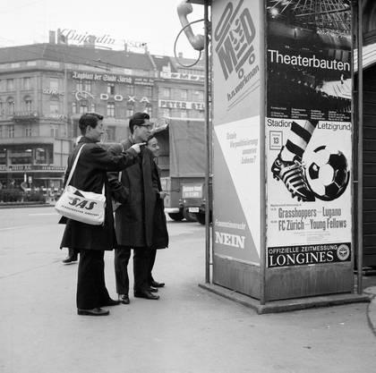 Japanische Touristen belächeln die Nein-Parole auf einem Abstimmungsplakat zum Frauenstimmrecht  in Zürich, aufgenommen 1966. Japan hatte dieses 21 Jahre zuvor einführt
