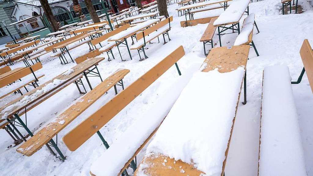 Schnee liegt auf Bierbänken in einem Biergarten im Stadtteil Haidhausen in München. Foto: Peter Kneffel/dpa