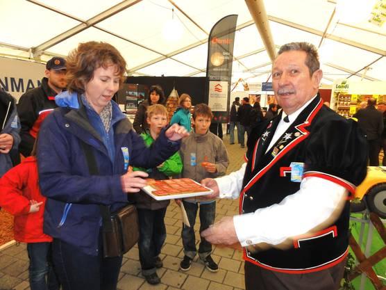 Hansueli Joost vom Jodlerklub Bützberg bietet dieser Büga-Besucherin einen von total 1000 Lebkuchen an