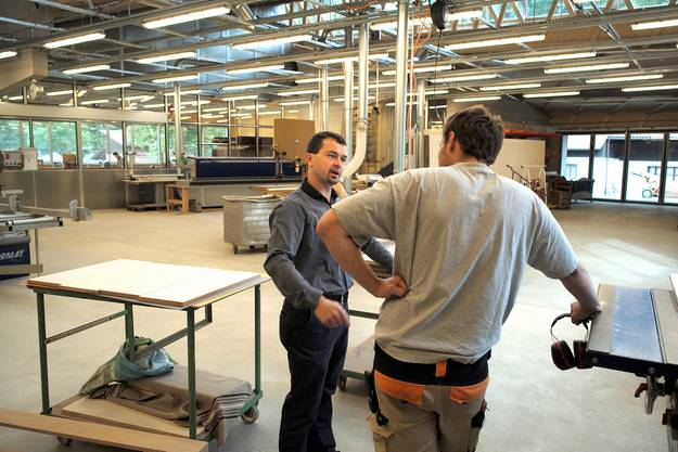 Pascal Brenner im Gespräch mit einem Betreuer im Neubau des Werkstattgebäudes in der Schreinerei.
