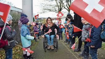 Catherine Debrunner bahnt sich ihren Weg durch die jubelnden Schülerinnen und Schüler der Primarschule Waltenschwil. Bild: Simon Kuhn