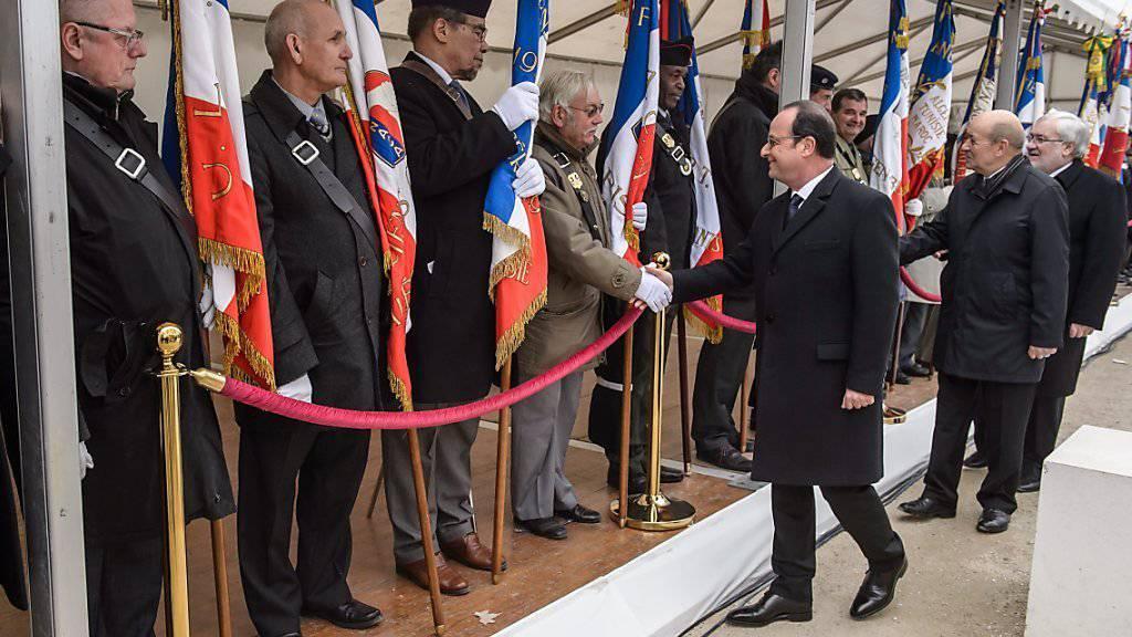 Frankreichs Präsident François Hollande schüttelt in Paris die Hände von Veteranen des Algerienkriegs
