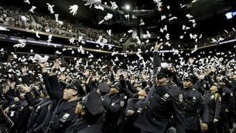 Grund zum Jubeln: Frischgebackene New Yorker Polizisten werfen nach einer Abschlusszeremonie an der Polizeiakademie ihre Handschuhe in die Luft