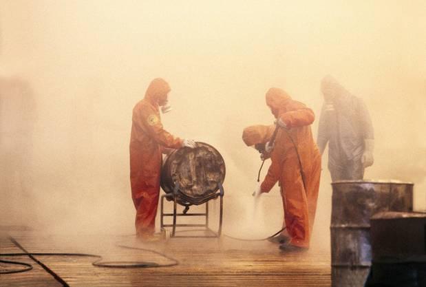 Mitglieder des Seuchenkommandos bei den Aufräumarbeiten nach der Brandkatastrophe vom 1. November 1986 in Schweizerhalle nahe Basel. Ueber 8'000 Fässer enthalten den ganzen giftigen Abfall der Sandoz-Katastrophe.
