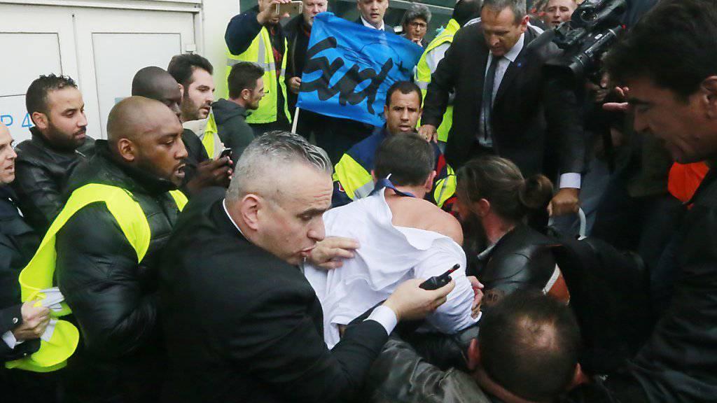 Der Air-France-Personalchef Xavier Broseta (in der Mitte, mit dem Rücken zur Kamera) musste vor den Angriffen wütender Angestellter vom Air-France-Hauptsitz fliehen. Nun wurden Verdächtige festgenommen.
