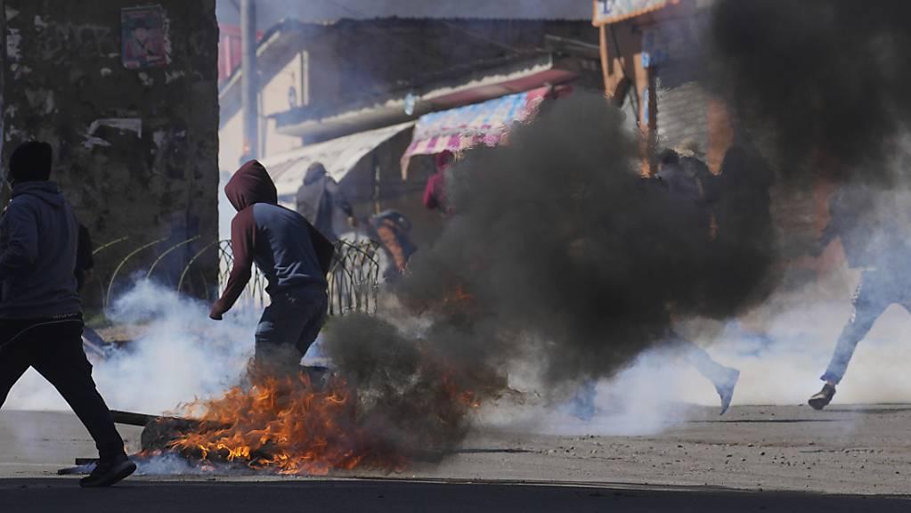 Kokabauern fliehen vor Tränengas, das von der Polizei in La Paz abgefeuert wurde. Die regierungsfeindlichen Kokabauern versuchten, den Kokamarkt mit Gewalt zu übernehmen, nachdem sie die Kontrolle verloren hatten, als eine andere Gruppe von Kokabauern einen neuen Anführer wählte.