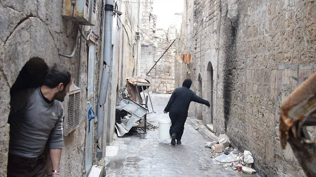 Eine Frau trägt Wasser zu ihrem Haus im Osten Aleppos: Mehrere Rebellengruppen werfen der syrischen Regierung vor, gegen die vereinbarte Waffenruhe zu verstossen. (Archivbild)