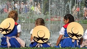 Drei Trachtenmädchen erholen sich am heissen Eröffnungstag des Unspunnenfests beim Wasserspiel im Interlakner Kursaalgarten.