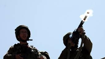 Israelische Soldaten schiessen Tränengasgranaten auf die Demonstranten.