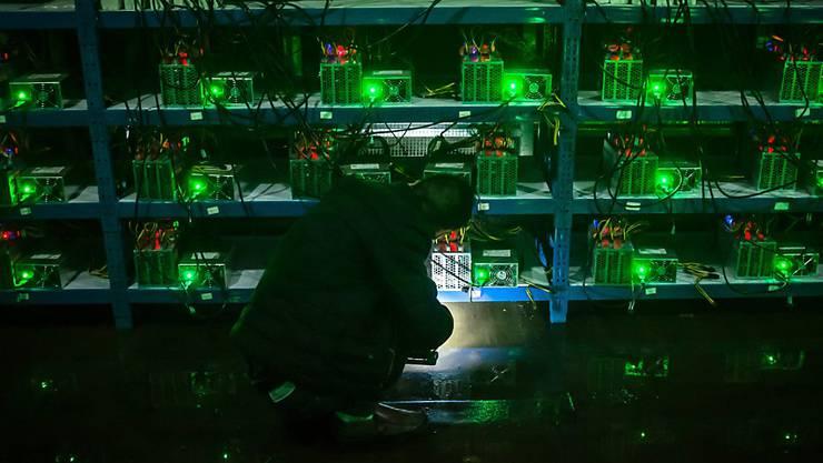 Ein Bitcoin-Schürfer nimmt die Mining-Maschinen in einer chinesischen Provinz in Augenschein. Die chinesische Regierung will das Schürfen von Digitalwährungen unterbinden. (Archiv)