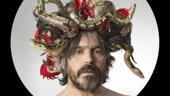 Für Koen Vanmechelen durchdringt das Huhn alle künstlerischen Formen und Dimensionen: Der belgische Künstler mit seinem Kopfschmuck aus Schlangen und Hühnerköpfen.