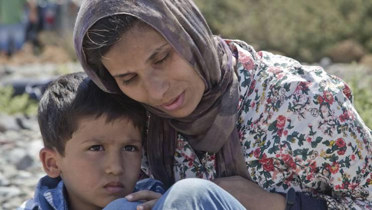 Eine Migrantin aus Afghanistan mit ihrem Sohn am Strand von Eftalou im Norden der griechischen Ägäisinsel Lesbos. Die Flüchtlinge hoffen, von Lesbos aus ans Festland zu gelangen. Von dort wollen sie über die Balkanroute nach Westeuropa (Archiv)