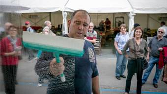 Ein Schausteller erklärt den Besuchern an der Messe Bauen und Wohnen im Tägerhard Wettingen eine neue Reinigungsmethode für Fenster.