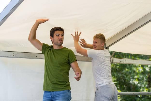 Trainer João Paiva (links) und Stürmer Blazenko Klaric spannen das Sonnensegel auf.