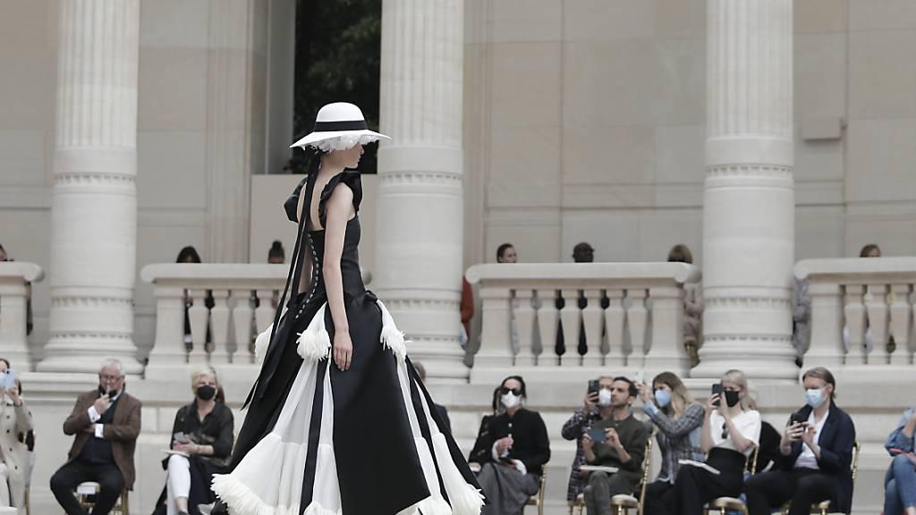 Ein Model geht während der Haute-Couture-Modenschau für die Herbst/Winter 2021/2022 Kollektion aus dem Modehaus Chanel über den Laufsteg. Foto: Lewis Joly/AP/dpa