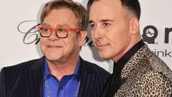 Elton John (l) und sein Mann David Furnish haben sich in den Ferien in Frankreich von Medien verleumdet gefühlt (Archiv 2014)