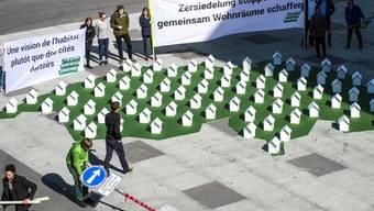 Mitglieder der Jungen Grünen positionieren Modell-Häuser in Bern