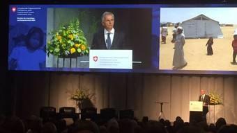 Bundesrat Didier Burkhalter an der Jahrestagung der Humanitären Hilfe, mit dem Foto eines Flüchtlingslagers