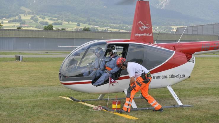 Flughelfer befestigt einen Kessel mit Wasser an einem Seil, das der Co-Pilot in der Hand hält.