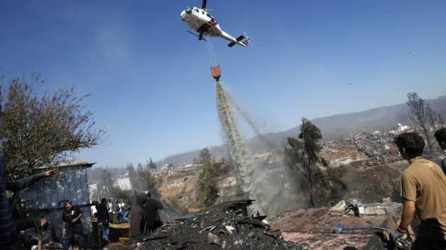 Löschhelikoper schüttet Wasser über einen Brandherd in Valparaiso