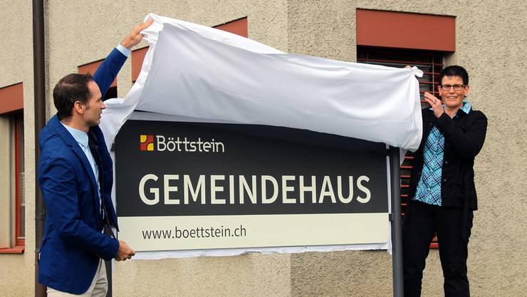 Gemeindeammann Patrick Gosteli und Gemeindeschreiberin Claudia Hess enthüllen die Tafel mit dem neuen Logo.