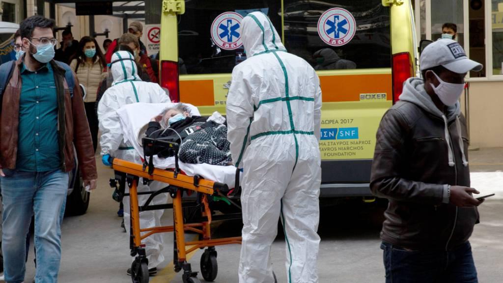 Medizinische Mitarbeiter in Schutzausrüstung transportieren einen Patienten auf einer Trage, um ihn in einem Krankenhaus in Athen zu verlegen. Foto: Marios Lolos/Xinhua/dpa