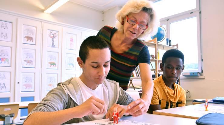 Die Integrationsklassenlehrerin leitet die Schüler, beziehungsweise deren Figuren über das Papierfeld.