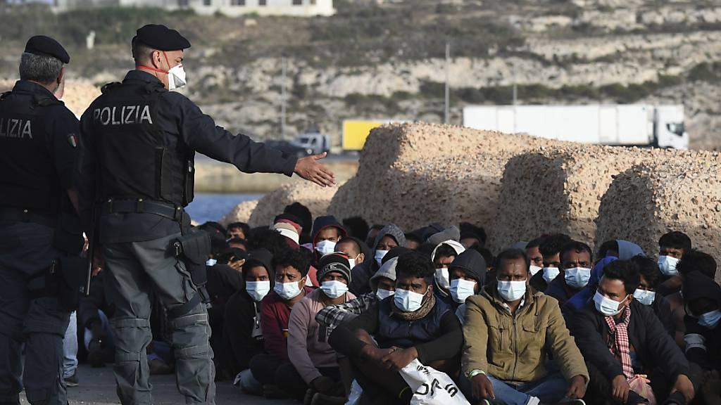dpatopbilder - Italienische Polizisten  und eine Gruppe Migranten:. Auf der kleinen italienischen Mittelmeerinsel Lampedusa sind innerhalb kurzer Zeit mehr als 2000 Bootsmigranten angekommen. Foto: Salvatore Cavalli/AP/dpa