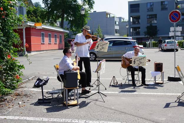 """Als """"Trio Zupfgeigen"""" boten Daniele Iannello (rechts) sowie Denise und Richard Wettmann Unterhaltung aus verschiedenen Musikstilen von klassisch über Flamenco bis Latin-Jazz. """"Wie freuen uns, dass es auch auf dem Seifi-Parkplatz so viel Publikum hat"""", erklärte Denise Wettmann. Später spielten die drei noch am Grabenweg."""