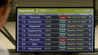 Ein Passagier studiert im Flughafen Haneda in Tokio die Informationen zu den Flügen.