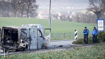 Polizisten begutachten am Tag nach dem Überfall den ausgebrannten Geldtransporter. (KEYSTONE/Laurent Gillieron)