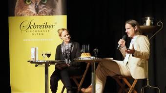 Der Philosoph Richard David Precht auf der Schützi-Bühne im Gespräch mit Nicola Steiner, der Moderatorin des SRF-Literaturclubs. Auf dem Tisch vor ihm steht ein Gugelhupf als Geburtstagstorte für 90 Jahre Buchhandlung Schreiber.