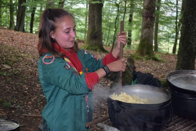 Ein Pfadi-Mädchen kocht zum Mittagessen Teigwaren.