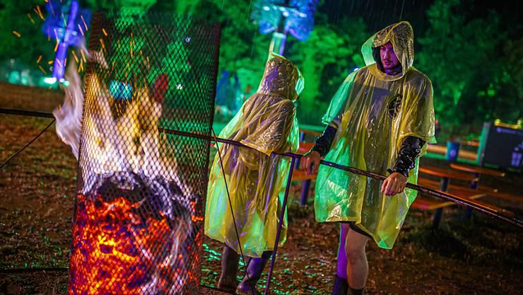 Das 44. Paléo Festival in Nyon ging am Sonntag zu Ende: Auch der Regen konnten dem Openair nichts anhaben. Besucher in Regenpellerinen stehen an einer Feuerstelle.