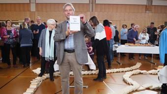 Der neue Gemeindeammann Urs Burkhard hält den «Stein des Anstossens» in der Hand. Am Boden liegen die umgefallenen Dominosteine.