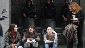 Wie weiter in Zypern? Bankangestellte sitzen während einer Protestkundgebung vor dem Bankgebäude. Im Hintergrund die Polizei.