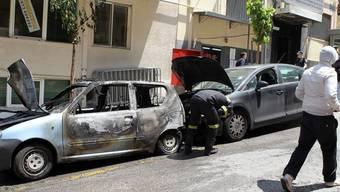 Vermummte Angreifer werfen Brandsätze gegen eine Polizeiwache in Athen