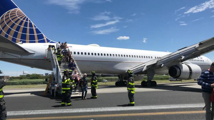 Rettungspersonal hilft bei der Evakuierung eines Flugzeugs der United Airlines, das auf dem Flughafen Newark bei New York teilweise von der Landebahn abgekommen ist.  (Caroline Craddock via AP)