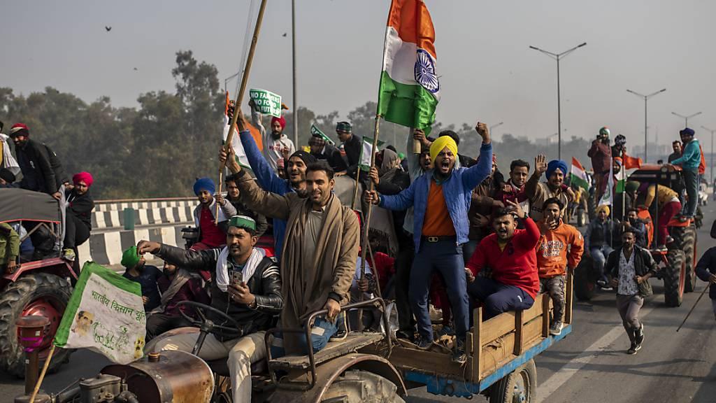 Indische Landwirte versammeln sich auf Traktoren zu einem Protest gegen neue Landwirtschaftsgesetze, während das Land zur gleichen Zeit den «Tag der Republik» mit einer Militärparade feiert. Foto: Altaf Qadri/AP/dpa