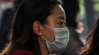 Eine Person schützt sich mit einer Gesichtsmaske vor einer möglichen Ansteckung mit dem Coronavirus. (Symbolbild)