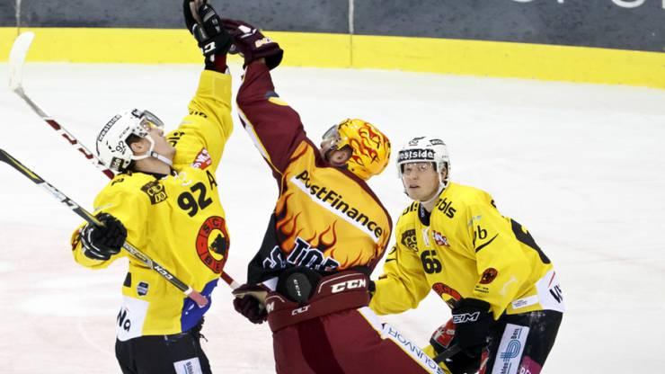 Genève-Servettes Center Tanner Richard greift gegen Berns Gaëtan Haas und Ramon Untersander nach dem Puck.